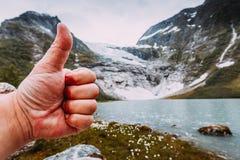 Αρσενικό χέρι που παρουσιάζει όπως με τον αντίχειρα επάνω στο υπόβαθρο βουνών Στοκ εικόνα με δικαίωμα ελεύθερης χρήσης