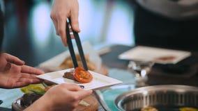 Αρσενικό χέρι που τίθεται ψημένα στη σχάρα στο πιάτο κρέας και τα λαχανικά απόθεμα βίντεο