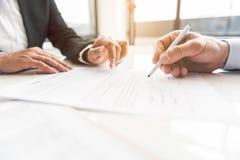 Αρσενικό χέρι που υπογράφει τη σύμβαση στο γραφείο στοκ εικόνες