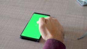 Αρσενικό χέρι στον πίνακα σχετικά με μια πράσινη χλεύη χρώματος οθόνης επάνω απόθεμα βίντεο