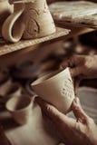 Αρσενικό χέρι του αγγειοπλάστη που εξετάζει το φλυτζάνι αργίλου Στοκ Εικόνες