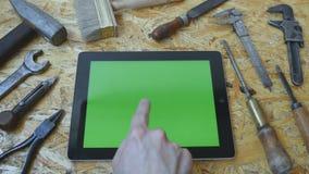 Αρσενικό χέρι του χειροτεχνικού βιοτέχνη που χρησιμοποιεί το PC ταμπλετών με την πράσινη οθόνη στο εργαστήριο Τοπ όψη Τα διαφορετ απόθεμα βίντεο