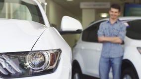Αρσενικό χαμόγελο πελατών που εξετάζει το νέο αυτοκίνητο στον αντιπρόσωπο απόθεμα βίντεο