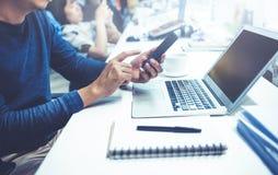 Αρσενικό χρησιμοποιώντας lap-top υπολογιστών και έξυπνο τηλέφωνο στην αρχή Στοκ εικόνα με δικαίωμα ελεύθερης χρήσης
