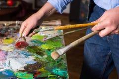 Αρσενικό artist& x27 εκμετάλλευση χεριών του s pallete khife και βούρτσες χρωμάτων Στοκ φωτογραφία με δικαίωμα ελεύθερης χρήσης