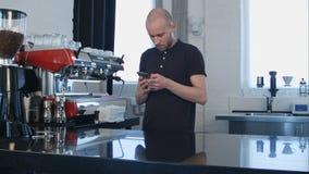 Αρσενικό barista χρησιμοποιώντας το smartphone στο χώρο εργασίας Στοκ εικόνες με δικαίωμα ελεύθερης χρήσης