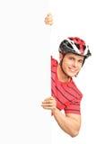 Αρσενικό bicyclist που φορά το κράνος και την τοποθέτηση Στοκ Φωτογραφίες