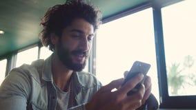 Αρσενικό Blogger χρησιμοποιώντας το έξυπνο τηλέφωνο στον καφέ απόθεμα βίντεο
