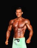 Αρσενικό Bodybuilder με τους πράσινους κορμούς και τις δερματοστιξίες Στοκ Εικόνες