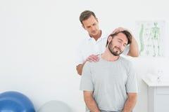 Αρσενικό chiropractor που κάνει τη ρύθμιση λαιμών Στοκ Φωτογραφίες