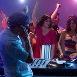 Αρσενικό DJ που αναμιγνύει τη μουσική στο συμβαλλόμενο μέρος με τους χορεύοντας ανθρώπους Στοκ εικόνα με δικαίωμα ελεύθερης χρήσης