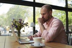Αρσενικό freelancer που συνδέει με το ραδιόφωνο μέσω του φορητού προσωπικού υπολογιστή στοκ εικόνες