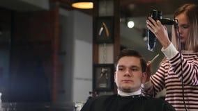 Αρσενικό hairstyle στο σαλόνι Ξήρανση τρίχας ατόμων στο κατάστημα κουρέων Τρίχα προσδιορισμού κουρέων με το στεγνωτήρα Τελειώστε  φιλμ μικρού μήκους