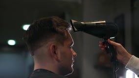 Αρσενικό hairstyle στο σαλόνι Ξήρανση τρίχας ατόμων στο κατάστημα κουρέων Τρίχα προσδιορισμού κουρέων με το στεγνωτήρα Τελειώστε  απόθεμα βίντεο