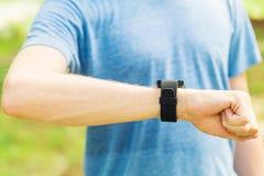 Αρσενικό jogger έξω από την εξέταση το έξυπνο ρολόι Στοκ φωτογραφίες με δικαίωμα ελεύθερης χρήσης