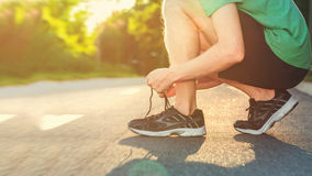 Αρσενικό jogger που δένει τα τρέχοντας παπούτσια του στο ηλιοβασίλεμα Στοκ Εικόνες
