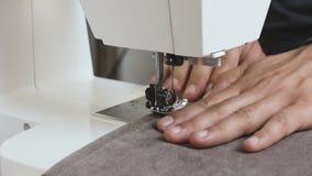 Αρσενικό seamstress ύφασμα εκμετάλλευσης χεριών πίσω από τη ράβοντας μηχανή φιλμ μικρού μήκους