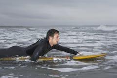 Αρσενικό Surfer που κωπηλατεί στην ιστιοσανίδα στο νερό στην παραλία στοκ φωτογραφίες