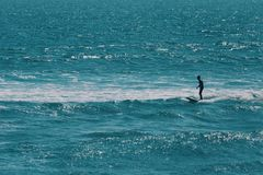 Αρσενικό surfer που περιμένει το μεγαλύτερο κύμα στον ωκεανό στοκ εικόνα