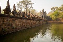 Αρχαία γέφυρα πέρα από την τάφρο γύρω από Angkor Thom στη νότια πύλη Στοκ Εικόνες