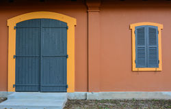 Αρχαία γκρίζα πόρτα, γκρίζο παράθυρο και κόκκινος τοίχος Στοκ Εικόνες