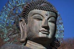 Αρχαία γλυπτική μετάλλων κινηματογραφήσεων σε πρώτο πλάνο της ειρήνης Βούδας συνεδρίασης μπροστά από το βουνό δέντρων Στοκ Εικόνες