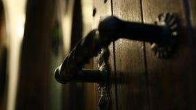 Αρχαία λαβή πορτών επεξεργασμένου σιδήρου στο σκοτεινό φως, είσοδος στο παλαιό μέγαρο, μυστικό φιλμ μικρού μήκους
