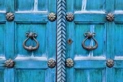 Αρχαία ξύλινη φωτεινή τυρκουάζ πόρτα με τις ηλικίας λαβές και τα καρφιά πορτών μετάλλων αρχιτεκτονικός όπως η ανασκόπηση είναι μπ Στοκ Φωτογραφίες