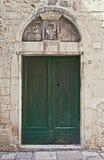 Αρχαία πόρτα που χρωματίζεται πράσινη με το architrave Στοκ Φωτογραφίες