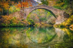 Αρχαία ρωμαϊκή γέφυρα που περιβάλλεται από τα κίτρινα δέντρα Στοκ εικόνα με δικαίωμα ελεύθερης χρήσης