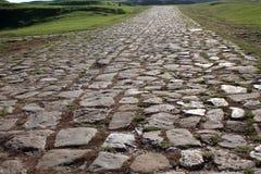 Αρχαίος δρόμος που στρώνεται με τον κυβόλινθο και να ανεβεί μέσω των λόφων Στοκ Εικόνες