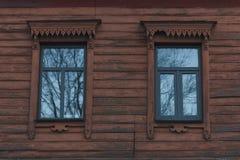 Αρχαίος ξύλινος τοίχος του παλαιού σπιτιού με τα παράθυρα στο χαρασμένο πλαίσιο Στοκ Φωτογραφία