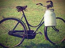 Αρχαίο αρμέγοντας ποδήλατο με το δοχείο γάλακτος στοκ φωτογραφία