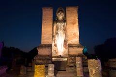 Αρχαίο γλυπτό του μόνιμου Βούδα στις καταστροφές Wat Mahathat στα φω'τα για το φωτισμό νύχτας Sukhothai, Ταϊλάνδη Στοκ Φωτογραφία