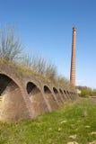 Αρχαίο εργοστάσιο τούβλου με τις τρύπες και την καπνοδόχο κλιβάνων τούβλου Στοκ φωτογραφία με δικαίωμα ελεύθερης χρήσης