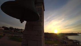 Αρχαίο κουδούνι στο υπόβαθρο της παραλίας στο ηλιοβασίλεμα απόθεμα βίντεο