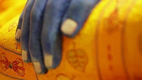 Αρχαίο μπλε και κίτρινο βουδιστικό άγαλμα - λεπτομέρεια του χεριού του Βούδα απόθεμα βίντεο