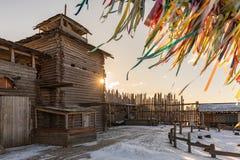 Αρχαίο ξύλινο φρούριο στο ηλιοβασίλεμα Ανάπτυξη των πολύχρωμων κορδελλών Στοκ Εικόνες