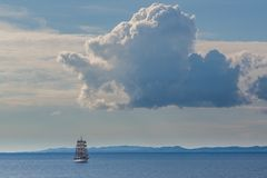 Αρχαίο πλέοντας σκάφος κάτω από την μπλε θάλασσα και τον ουρανό σύννεφων Στοκ εικόνες με δικαίωμα ελεύθερης χρήσης