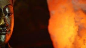 Αρχαίο χρυσό βουδιστικό scuplture με το πορτοκαλί φως στο σκοτεινό υπόβαθρο απόθεμα βίντεο