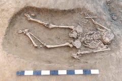 αρχαιολογική ανασκαφή Ανθρώπινα κόκκαλα, σκελετός και κρανίο υπολειμμάτων στο έδαφος, με τα μικρά χειροποίητα αντικείμενα ίδρυσης στοκ εικόνα