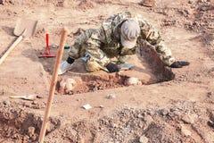 αρχαιολογική ανασκαφή Ο αρχαιολόγος που πραγματοποιεί την έρευνα για τα ανθρώπινα κόκκαλα, μέρος του σκελετού από το έδαφος, με τ στοκ εικόνες