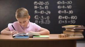 Αρχικές ασκήσεις γραψίματος μαθητών στο σημειωματάριο, που προετοιμάζει την εργασία, έξυπνο παιδί απόθεμα βίντεο