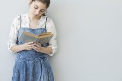 αρχικές νεολαίες ανάγνωσης κοριτσιών εστίασης προσώπου βιβλίων Στοκ φωτογραφίες με δικαίωμα ελεύθερης χρήσης