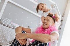 Αρχικό κορίτσι διασκέδασης που κάνει τον μπαμπά της αισθαμένος αρκετά Στοκ Εικόνα