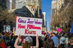 Αρχικό σημάδι που φέρεται από έναν από τους συμμετέχοντες στις γυναίκες ` s Μάρτιος στοκ φωτογραφία