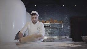 Αρχιμάγειρας άσπρο σε ομοιόμορφο απασχομένος στη γρήγορα κυλώντας ζύμη με τη μεγάλη ξύλινη κυλώντας καρφίτσα ζύμης στον πίνακα στ απόθεμα βίντεο