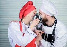 Αρχιμάγειρας ανδρών και γυναικών στο εστιατόριο πίσω από το μεταλλικό δίσκο μυστικό συστατικό από τη συνταγή μάγειρας ομοιόμορφος στοκ εικόνες