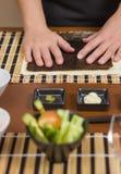 Αρχιμάγειρας γυναικών έτοιμος να προετοιμάσει τους ιαπωνικούς ρόλους σουσιών Στοκ Φωτογραφία