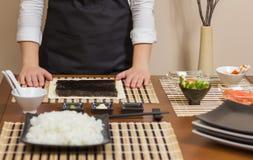 Αρχιμάγειρας γυναικών έτοιμος να προετοιμάσει τους ιαπωνικούς ρόλους σουσιών Στοκ εικόνα με δικαίωμα ελεύθερης χρήσης